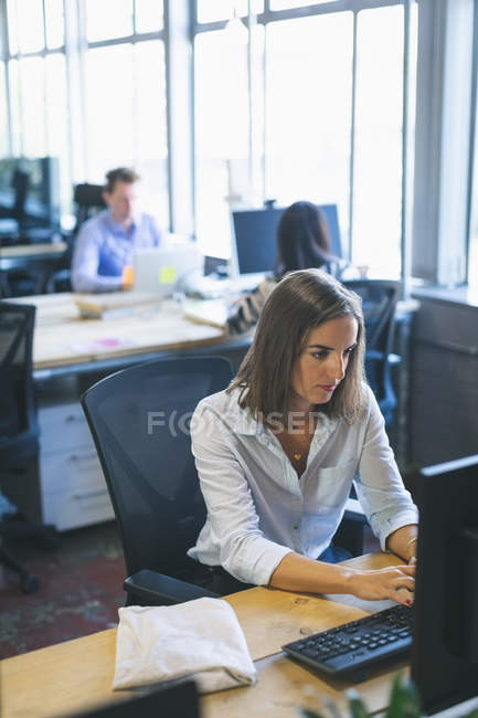 Female executive working on computer at desk in office — Stock Photo