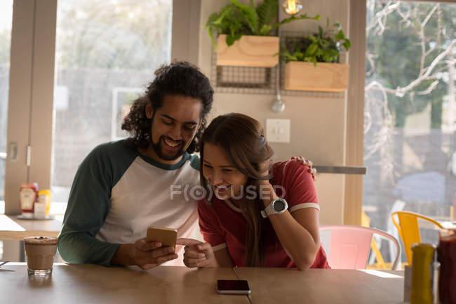 Щаслива пара використання мобільного телефону у кафе — стокове фото