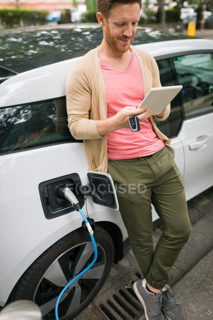 Homme utilisant une tablette numérique tout en rechargeant la voiture électrique à la station de charge — Photo de stock