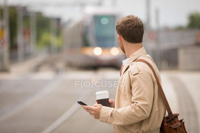 Людина за допомогою мобільного дивлячись на поїзді в платформи — стокове фото