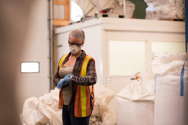 Female worker checking time on smart watch at warehouse — Stock Photo