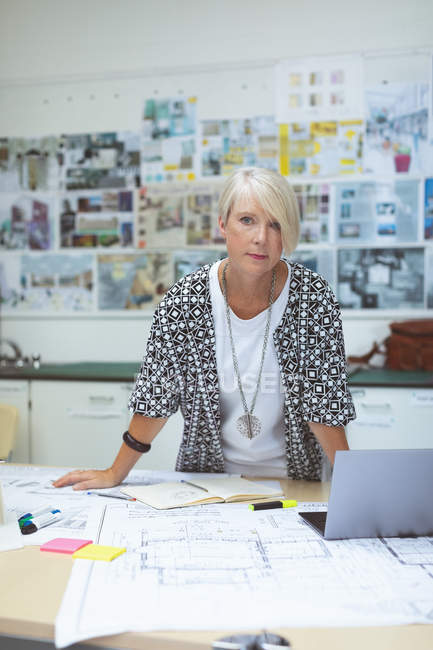 Portrait of female executive standing at desk in office — Stock Photo