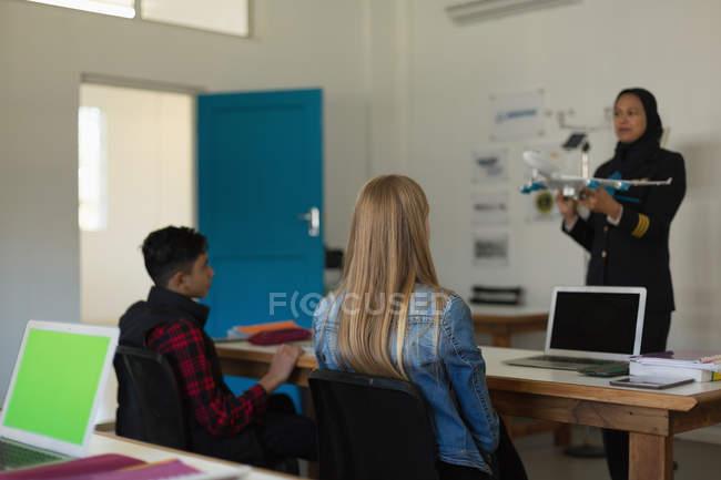 Femme pilote d'enseigner aux enfants à l'Institut de formation modèle réduit d'avion — Photo de stock