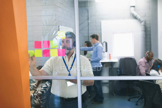 Male executive looking at sticky notes in office — Stock Photo