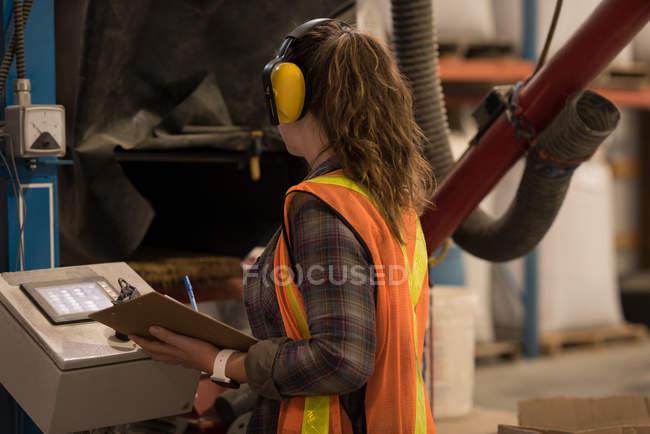 Female worker operating machine at warehouse — Stock Photo