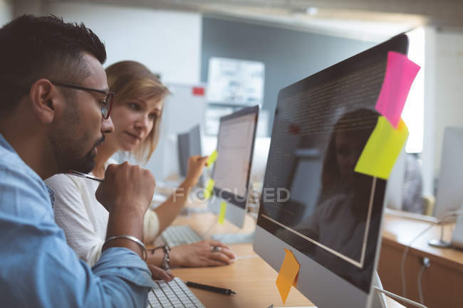 Side view of executives discussing over desktop pc at desk in office — Stock Photo