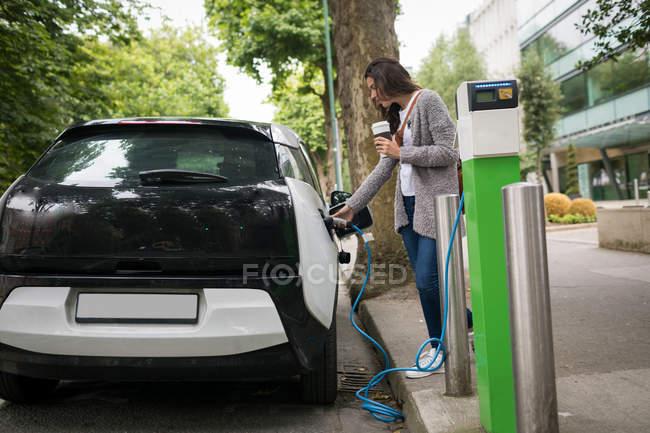Jeune femme recharge voiture électrique à la station de recharge — Photo de stock