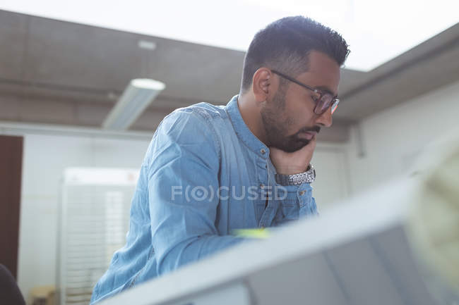 Thoughtful male executive working over drafting table in office — Stock Photo