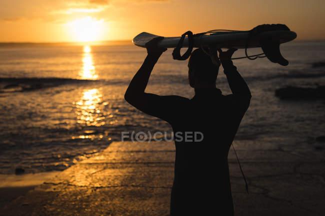 Surfista llevando la tabla de surf en su cabeza en la playa - foto de stock