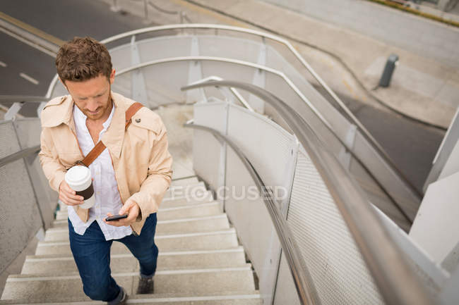 Smart man walking up stairs while using mobile phone — Stock Photo