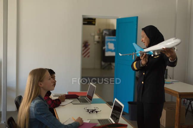 Female pilot teaching about model plane to kids in training institute — Stock Photo