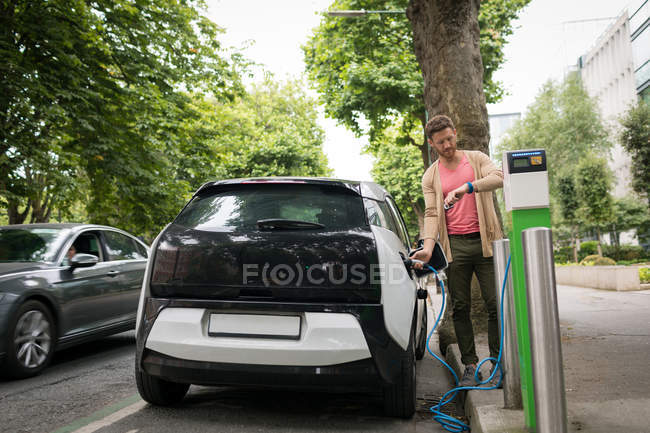 Man checking time on smart watch while charging electric car at charging station — Stock Photo