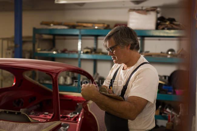 Hombre mecánico de escribir en el portapapeles en el garaje - foto de stock