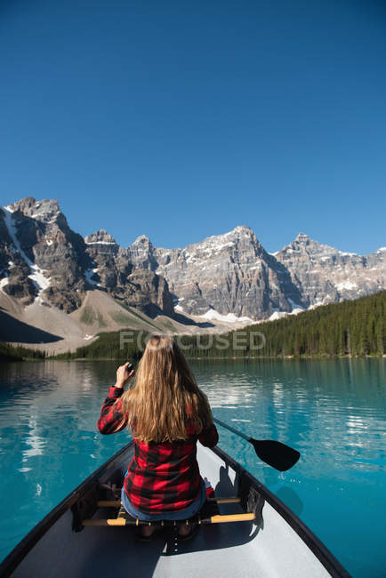 Vista posteriore della donna che naviga nel fiume in una giornata di sole — Foto stock