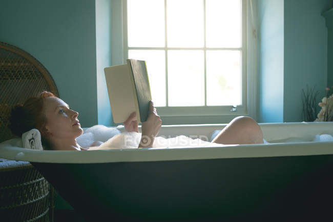 Woman reading book in bathtub at bathroom — Stock Photo
