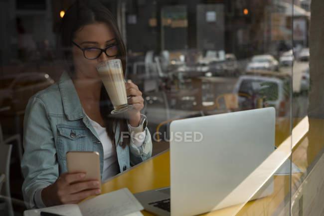 Женщина, имея кофе при использовании мобильного телефона в кафе — стоковое фото