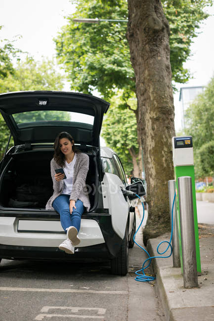 Woman using mobile phone while charging electric car at charging station — Stock Photo