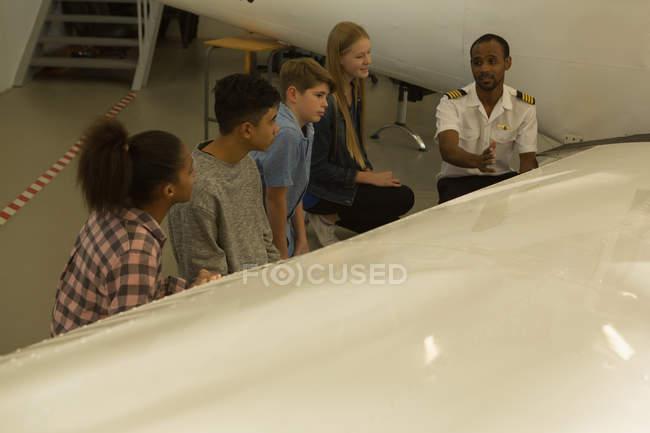 Pilote, un homme expliquant tout avion pour enfants à l'Institut de formation — Photo de stock