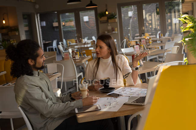 Business executive talking to each other in cafe — Stock Photo