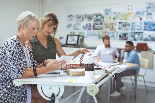 Female executives discussing over digital tablet on drafting table in office — Stock Photo
