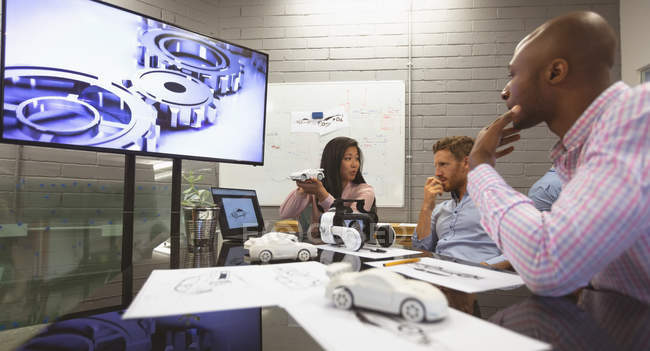 Business colleagues discussing over car model in office — Stock Photo