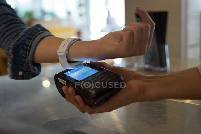 Close-up of woman paying with NFC technology on smartwatch in cafe — Stock Photo
