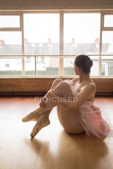 Bailarina atenciosa olhando através da janela enquanto sentado no chão de madeira no estúdio de dança — Fotografia de Stock