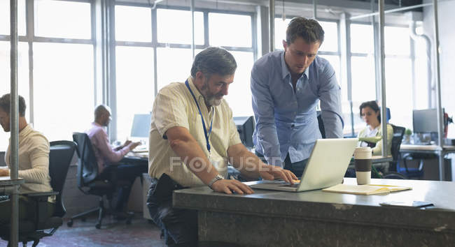 Деловые коллеги обсуждают за ноутбуком в офисе — стоковое фото