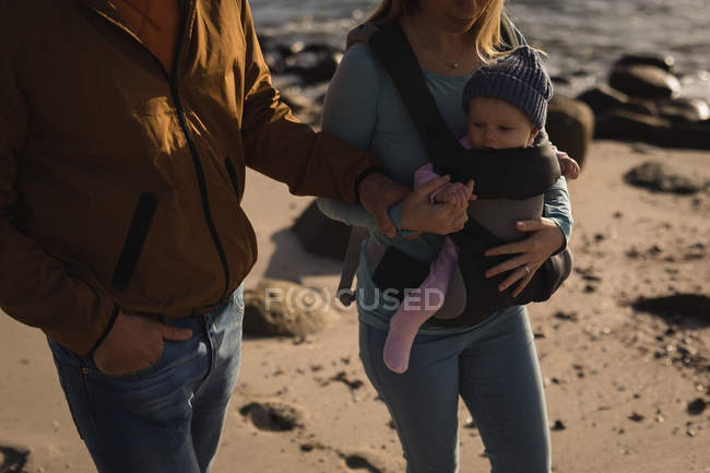 Mid section of parents with baby walking on beach — Stock Photo