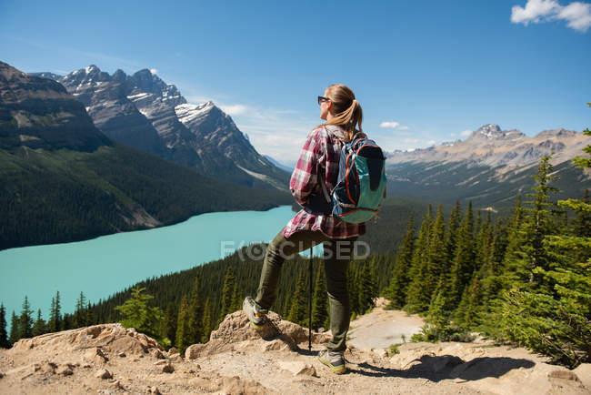 Caminhante feminina de pé com mochila no campo em um dia ensolarado — Fotografia de Stock