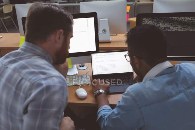 Задний вид руководителей обсуждающих за ноутбуком в офисе — стоковое фото