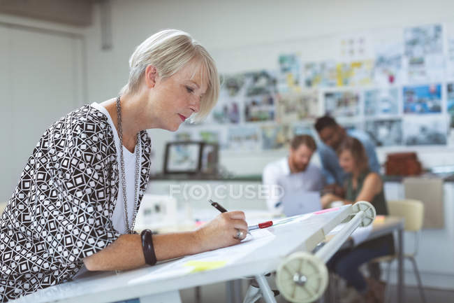 Female executive working on drafting table in office — Stock Photo