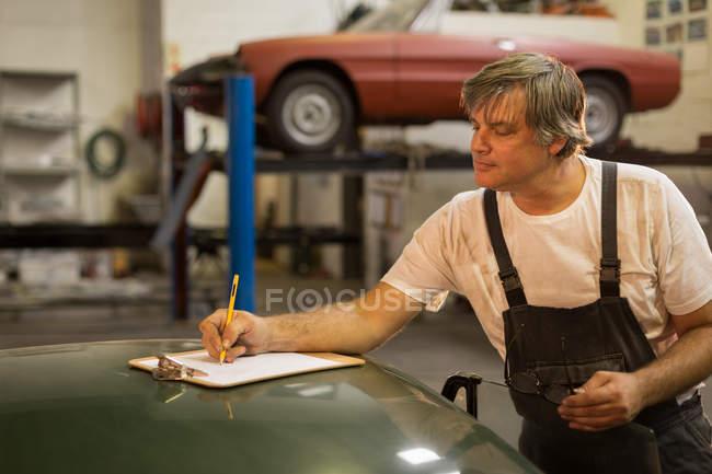 Male mechanic writing on clipboard in garage — Stock Photo