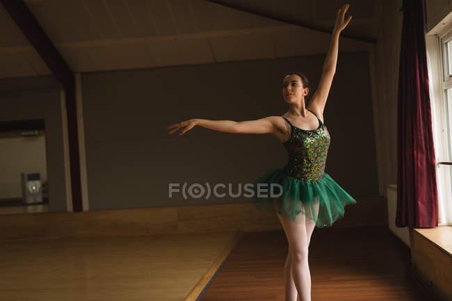 Beautiful ballerina practice arabesque ballet position in dance studio — Stock Photo