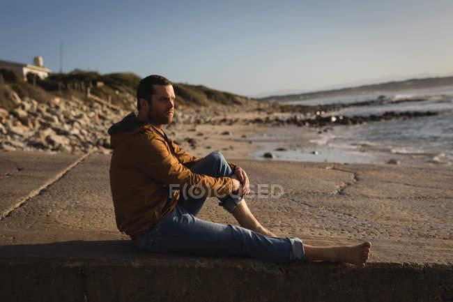 Nachdenklicher Mann sitzt auf Strandpromenade — Stockfoto