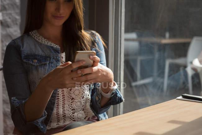 Donna che utilizza telefono mobile nella caffetteria — Foto stock