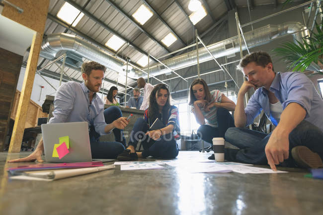 Business people discussing over documents in office — Stock Photo