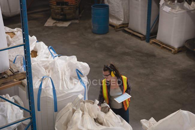 Lavoratrice con tablet digitale che controlla i grani nel magazzino — Foto stock