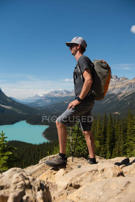 Vista lateral do jovem homem em pé sobre uma rocha — Fotografia de Stock