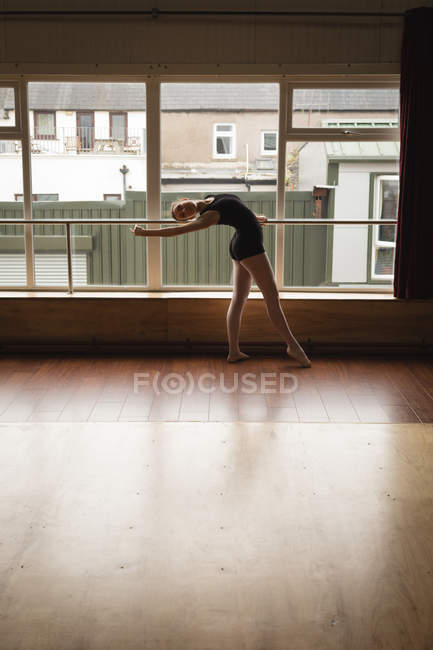 Ballerina practicing ballet dance near window in dance studio — Stock Photo