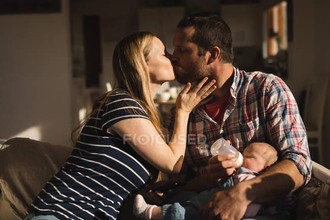 Eltern küssen sich, während Vater Baby zu Hause auf Sofa füttert — Stockfoto