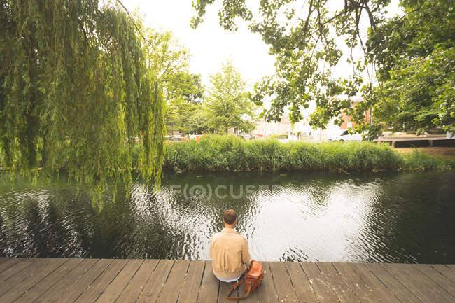 Rear view of man sitting near lake side — Stock Photo