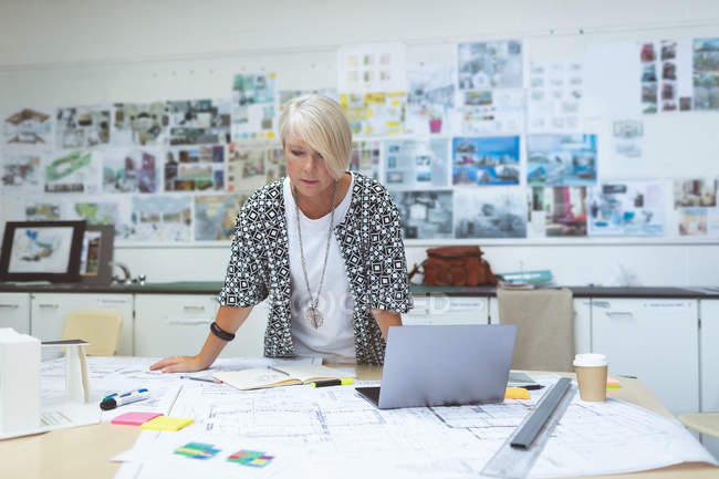 Female executive looking on blueprints at desk in office — Stock Photo