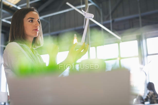 Female executive holding windmill model at desk in office — Stock Photo