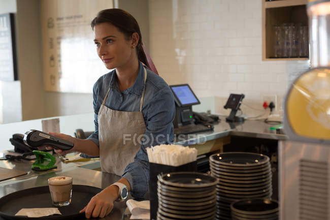 Waitress standing with NFC machine in cafe — Stock Photo