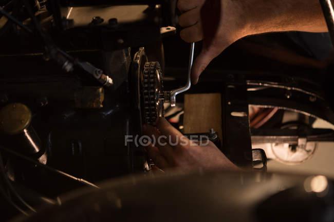 Mecánico masculino servicio de un coche en el garaje - foto de stock