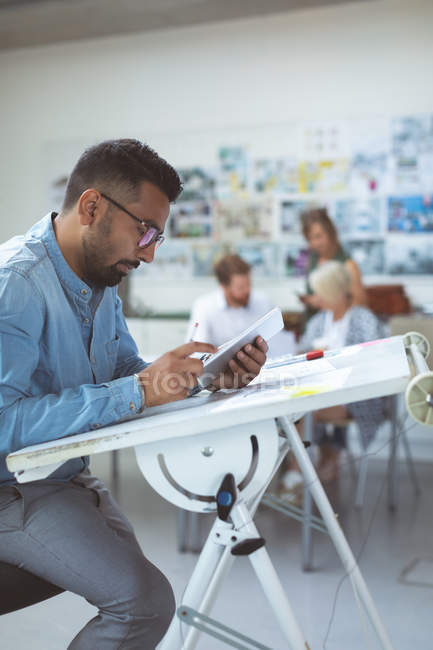 Executive using digital tablet on drafting table in office — Stock Photo