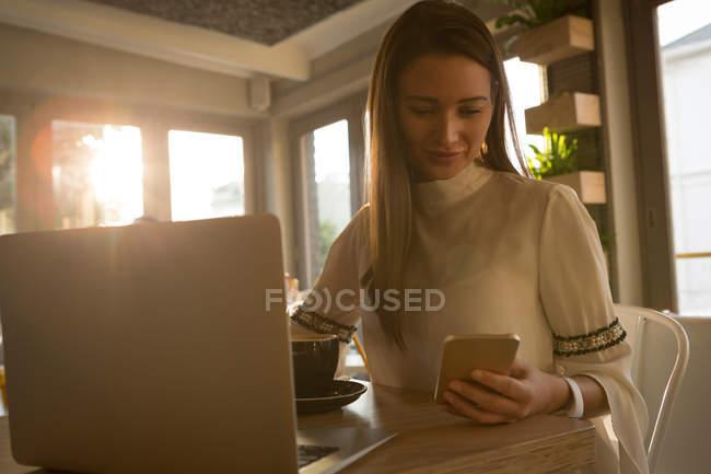 Молодая женщина, используя мобильный телефон в кафе — стоковое фото