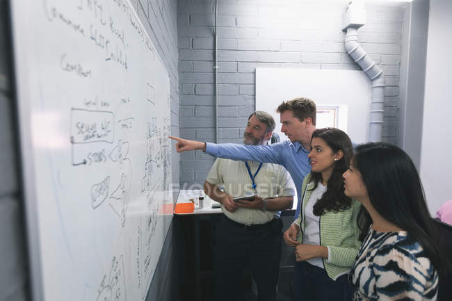 Business people discussing over whiteboard in office — Stock Photo