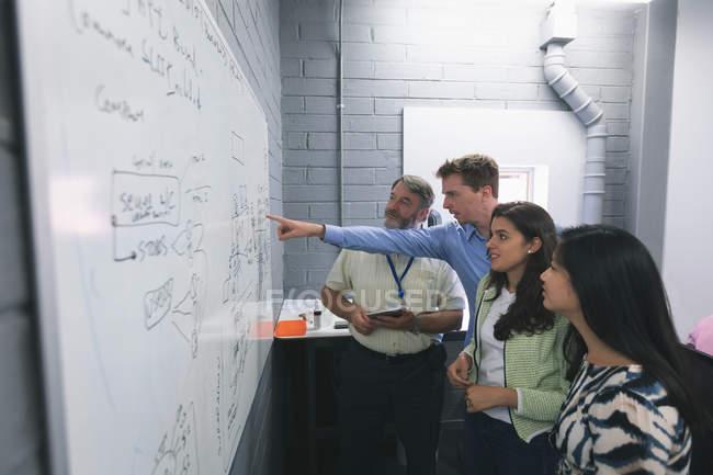 Geschäftsleute diskutieren über Whiteboard im Büro — Stockfoto